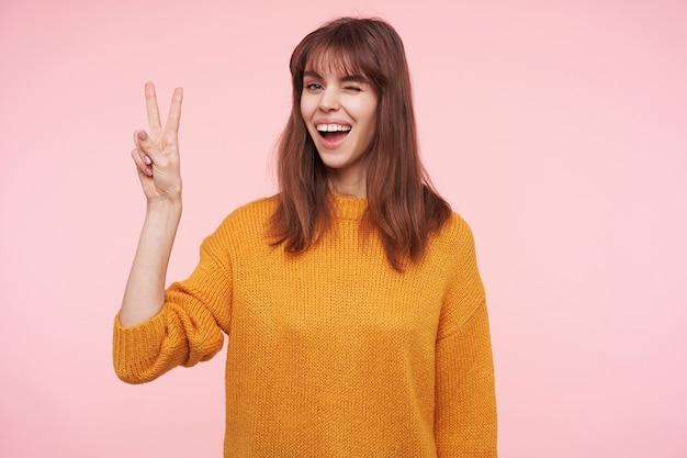 Jovem alegre muito morena com penteado casual, levantando a mão com gesto de vitória e dando uma piscadela enquanto sorri amplamente, em pé sobre a parede rosa