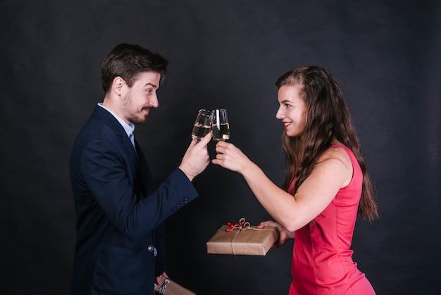 Jovem, alegre, mulher, agarrar, óculos, de, bebida, com, homem, e, segurando, presente, caixas
