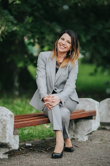 Jovem alegre mulher branca em uma linda roupa formal com terno cinza elegante e calça