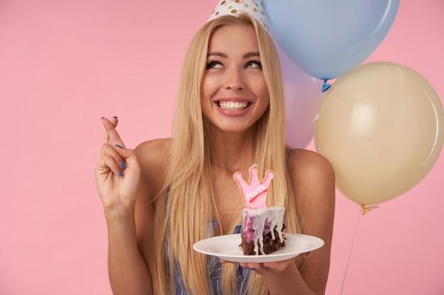 Jovem alegre mulher de cabelos compridos com longos cabelos loiros cruzando os dedos enquanto faz um pedido de aniversário, segurando um pedaço de bolo com uma vela sobre balões de ar multicoloridos e fundo rosa