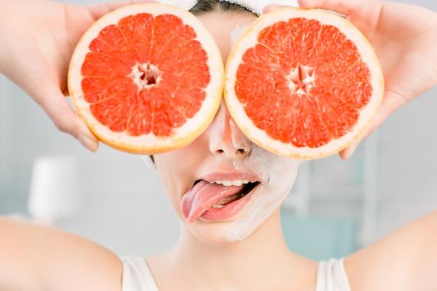 Jovem alegre mulher europeia com máscara facial branca e toalha branca na cabeça mostra a língua e mantém grandes toranjas, cobrindo os olhos dela. dieta saudável, skincare, tratamento facial, conceito de cosmetologia.