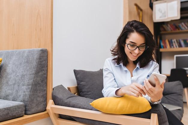 Jovem alegre mulher morena de óculos escuros relaxando no sofá em um apartamento moderno. usando telefone, mensagens de texto, sorrindo, humor alegre.