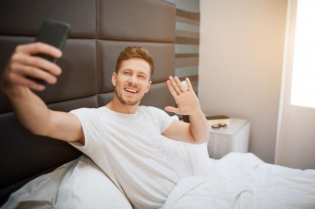 Jovem alegre na cama esta manhã. ele e posar na câmera do telefone. cara acenar com a mão e sorrir. luz do dia.