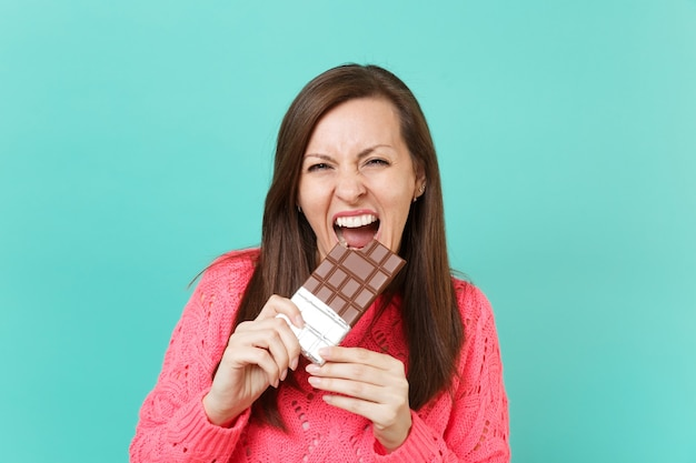 Jovem alegre na camisola de malha rosa, segurando na mão, mordendo e comendo a barra de chocolate isolada no fundo da parede azul turquesa, retrato de estúdio. conceito de estilo de vida de pessoas. simule o espaço da cópia.