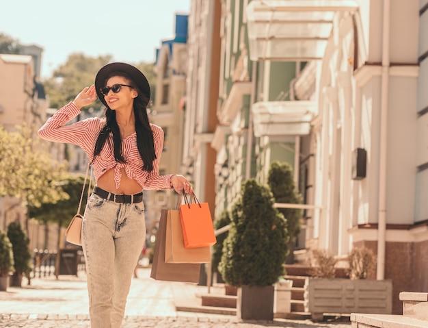 Jovem alegre na rua com sacolas de compras, caminhando e sorrindo. banner do site