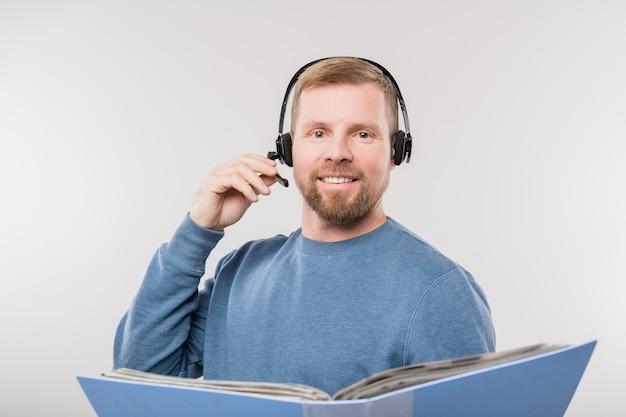 Jovem alegre operadora de linha direta segurando uma pasta aberta com documentos enquanto consulta clientes online de forma isolada