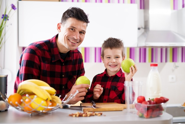 Jovem alegre pai e filho em camisas vermelhas, sentado no balcão da cozinha, sorrindo e segurando maçãs.