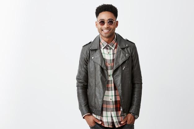 Jovem alegre pele bronzeada homem bonito com cabelo encaracolado na jaqueta de couro elegante e óculos de sol sorrindo segurando as mãos nos bolsos