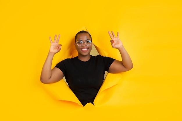 Jovem alegre posa em um buraco de papel amarelo rasgado
