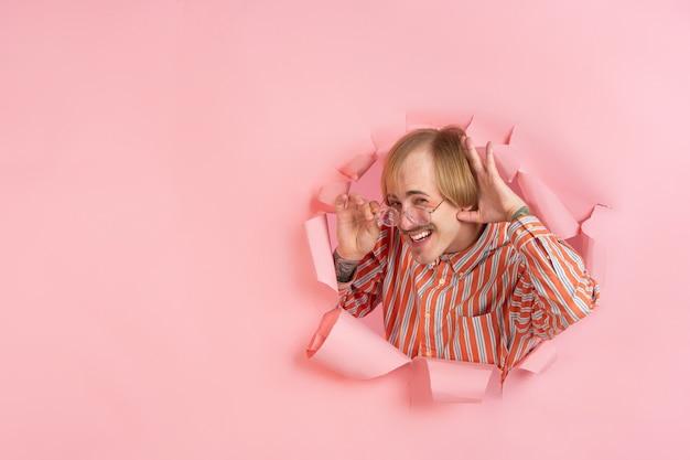 Jovem alegre posa emocionalmente e expressivamente em uma parede de buraco de papel coral rasgado