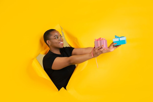 Jovem alegre posa emocionalmente e expressivamente na parede do buraco do papel amarelo rasgado