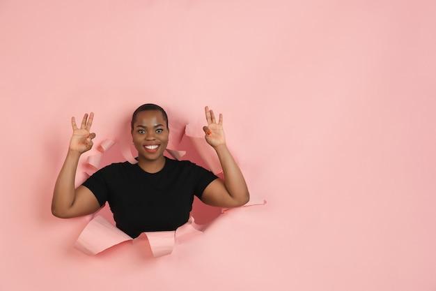 Jovem alegre posa emocionalmente e expressivamente na parede rasgada do buraco do papel coral