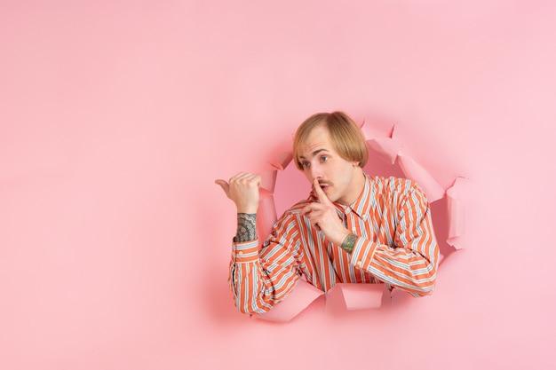 Jovem alegre posa na parede de um buraco de papel coral rasgado, emocional e expressivo