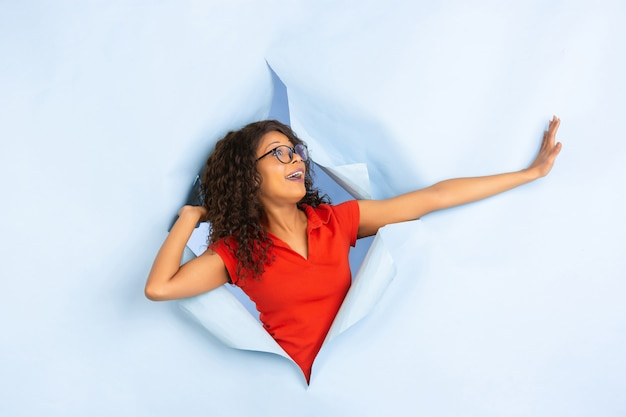 Jovem alegre posa no fundo do buraco de papel azul rasgado, emocional e expressivo