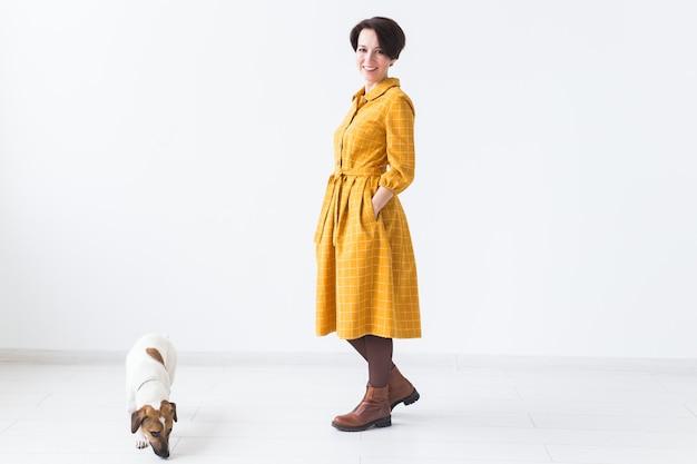 Jovem alegre posando em um vestido amarelo com seu amado cachorro jack russell terrier de pé em uma parede branca
