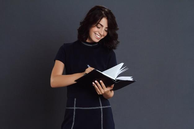 Jovem alegre posando sobre parede cinza e escrevendo no caderno
