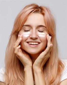 Jovem alegre positiva aplicar creme hidratante lifting nutritivo ou tratamento facial