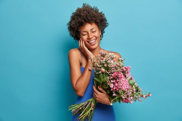 Jovem alegre, positiva, de pele escura, sorrindo feliz com os olhos fechados segurando um grande buquê de flores