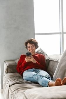 Jovem alegre relaxando em casa, ouvindo música com fones de ouvido sem fio