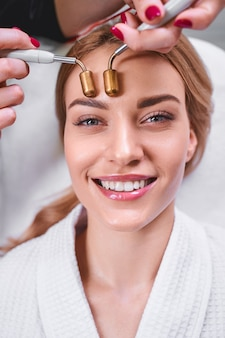 Jovem alegre se divertindo enquanto a cosmetologista usa um aparelho digital moderno para tratar seu rosto