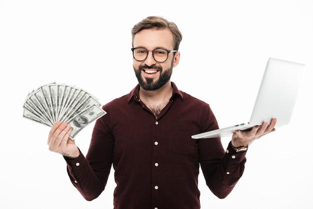 Jovem alegre segurando dinheiro e computador portátil.