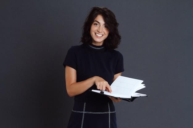 Jovem alegre segurando o caderno nas mãos