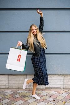 Jovem alegre segurando sacolas de compras equilibrando contra a parede