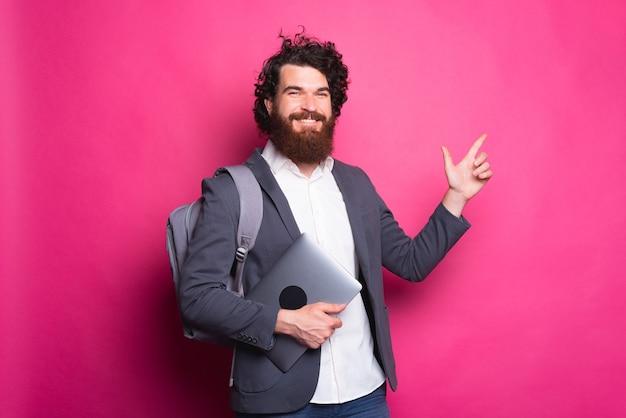 Jovem alegre segurando um computador com uma mochila apontando para a parede rosa atrás dele
