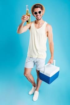 Jovem alegre segurando uma bolsa térmica e bebendo cerveja