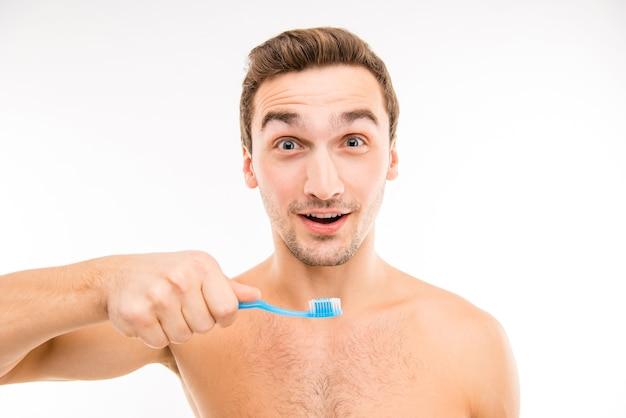 Jovem alegre segurando uma escova de dentes