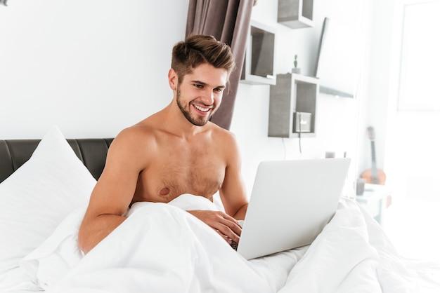 Jovem alegre sem camisa sentado e usando o laptop na cama