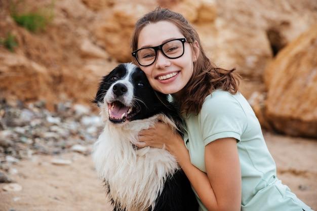 Jovem alegre sentada e abraçando o cachorro na praia