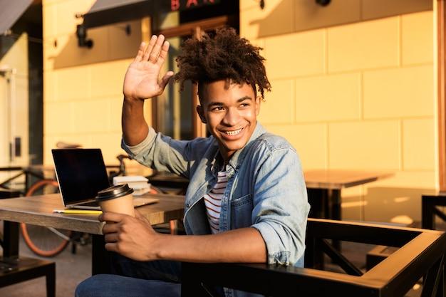 Jovem alegre sentado no café ao ar livre