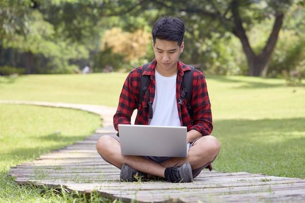 Jovem alegre sentado no parque usando um laptop