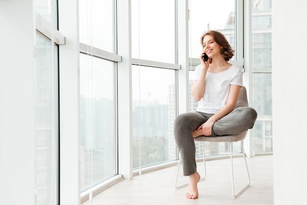 Jovem alegre sentado perto da janela, falando por telefone