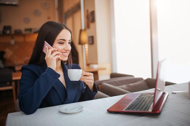 Jovem alegre sentar à mesa e trabalhar. ela sorri. o cliente fala ao telefone e olha para a tela do laptop. mulher jovem a beber café da chávena