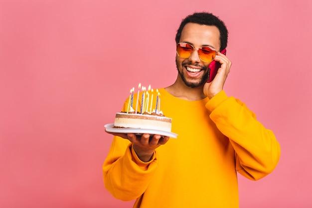 Jovem alegre soprando velas em um bolo de aniversário isolado em rosa. usando o celular.