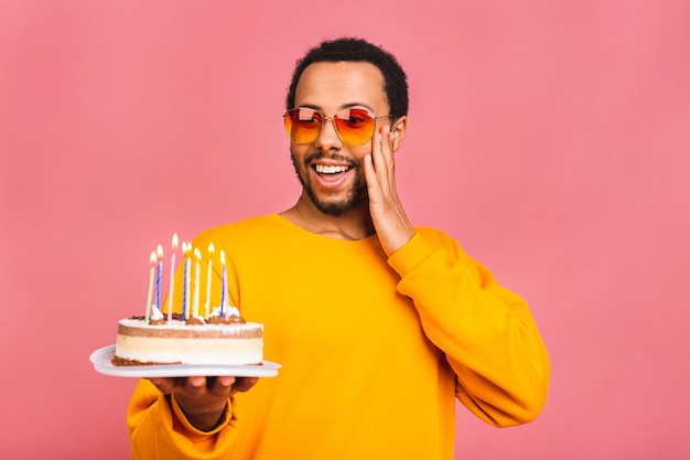 Jovem alegre soprando velas em um bolo de aniversário isolado em rosa.