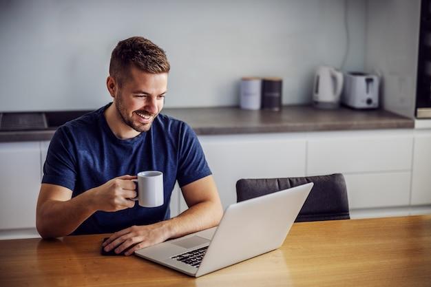Jovem alegre sorridente sentado à mesa de dinging, segurando a caneca com café fresco da manhã e olhando para o laptop. ele está recebendo curtidas para postar nas redes sociais.