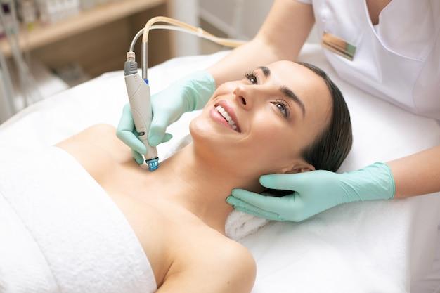 Jovem alegre sorrindo enquanto esteticista profissional com luvas de borracha usando um dispositivo especial para dermoabrasão na pele do pescoço