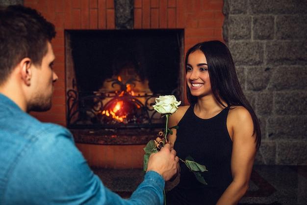Jovem alegre sorrir para o namorado. ela olha para ele. cara, dê-lhe uma rosa branca. eles se sentam à lareira.
