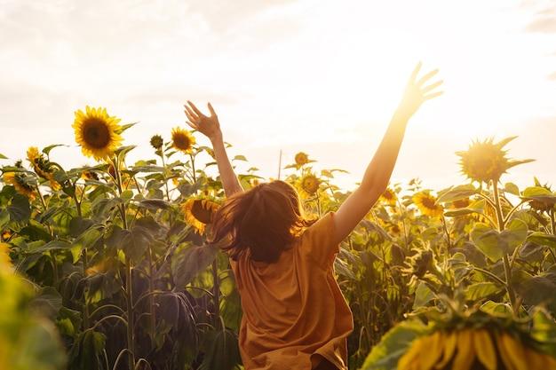 Jovem alegre sozinha entre um campo de girassóis vista de trás aproveite o momento da colheita