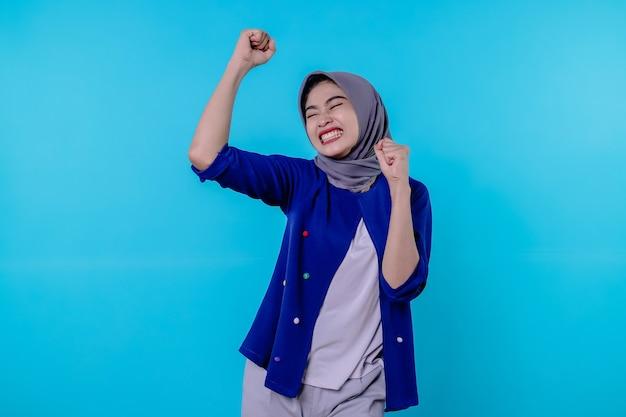 Jovem alegre tem uma expressão positiva, fecha os punhos, tem uma aparência radiante, estando em alto astral, usando um hijab, isolada sobre a parede azul
