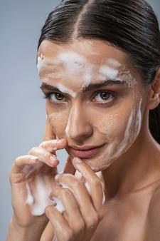 Jovem alegre usando espuma para tratamento facial