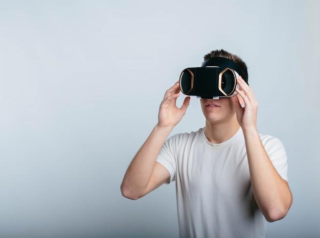 Jovem alegre usando fone de ouvido vr para experimentar a realidade virtual. esteja sozinho na sala e isolado no fundo branco. vídeo realista.
