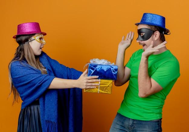 Jovem alegre usando máscara de baile de máscaras segurando caixas de presente, olhando para um homem bonito surpreso de chapéu azul usando máscara de baile de máscaras, levantando as mãos olhando para as caixas