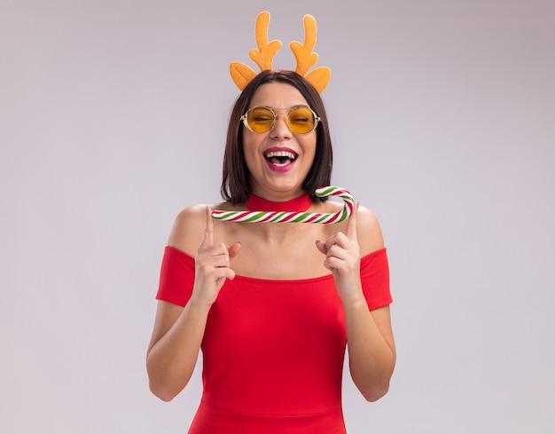 Jovem alegre usando uma bandana de chifres de rena e óculos segurando uma bengala de natal natal rindo com os olhos fechados, isolado no fundo branco