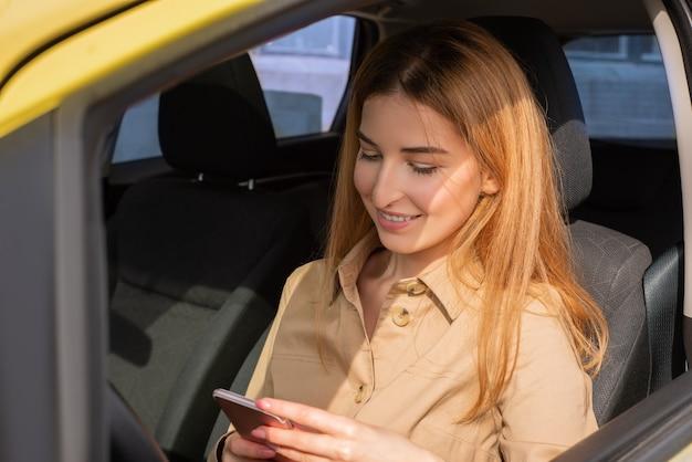 Jovem alegre verificando seu smartphone enquanto está sentada no banco do motorista de seu carro amarelo