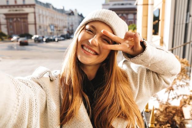 Jovem alegre vestida com um casaco outono e chapéu ao ar livre, tirando uma selfie e mostrando paz