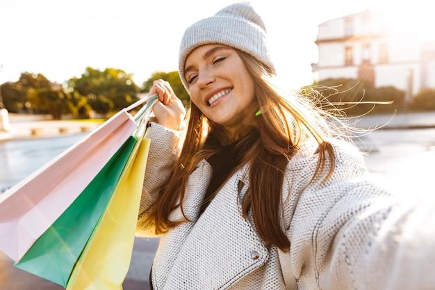 Jovem alegre vestida com um casaco outono e chapéu caminhando ao ar livre na rua da cidade, carregando sacolas de compras, tirando uma selfie